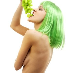 green hair girl with a bunch of grapes over white